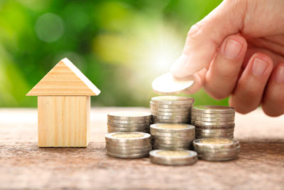 Mortgage advice concept. Stacks of coins stand next to a small wooden house. A man's hand adds a coin to one stack.