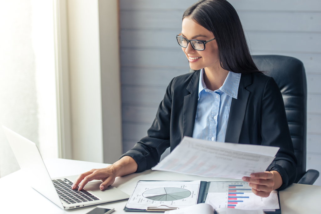 A young female financial adviser uses a laptop as she examines financial advice reports. She is smartly dressed and smiling.